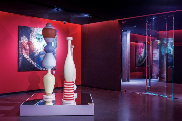Hall de distribución del hotel Nhow Milano con tótems de cerámica de Matteo Thun frente a un retrato de la serie DV37 de Gian Piero Gasperini.