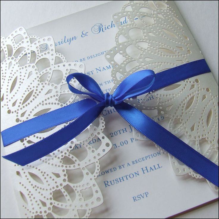 This laser cut wedding invitation is finished with a satin ribbon bow and crystals.