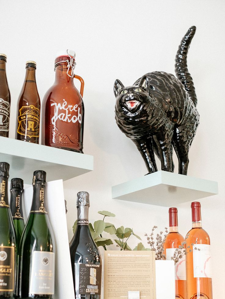 A detail of the well stocked shelves above the counter, craft beer and award winning wines, with a very happy cat keeping watch, Ou Bien Encore Geneva.