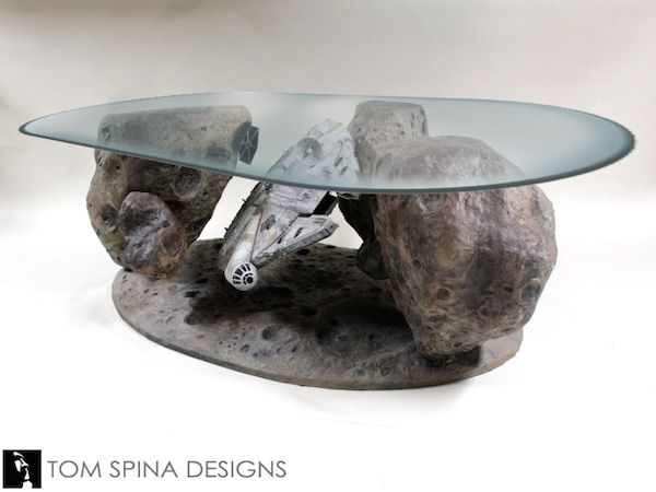 This is an impressive coffee table from Tom Spina Designs. We've the Millennium Falcon in it's famous game of hide and seek among dangerous asteroids. You can even see a Tie-Fighter trying to get a look around the other side.