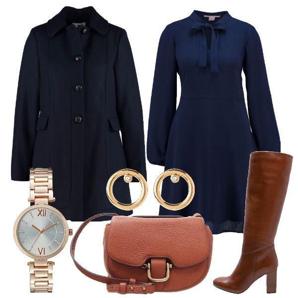 Vestito blu scampanato con maniche a palloncino e fiocco al collo, cappotto navy, stivali e borsa a tracolla color cuoio. Ad illuminare il tutto, gli orecchini con brillantino e l'orologio oro rosa.