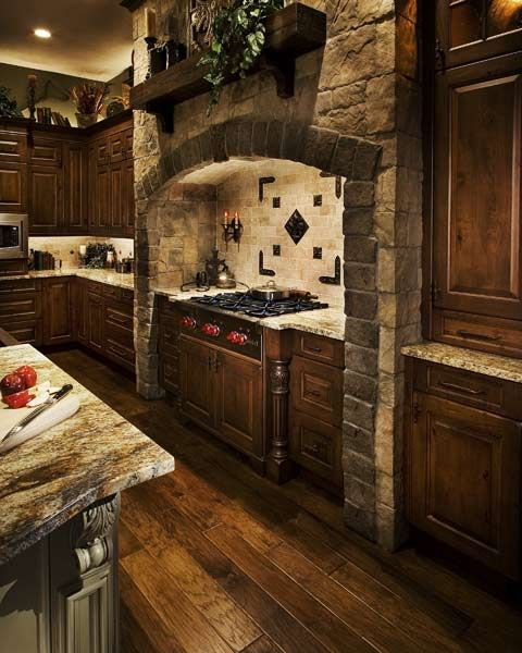 "Designed to resemble a castle's ""walk-in cooking fireplace,"" this modern hearth features a cultured stone hood surround over a six-burner Wolf rangetop, granite countertop, and a tumbled limestone backsplash with bronze inlays. A 200-year-old reclaimed wood mantel completes the look. (This is an awesome kitchen!!!)"