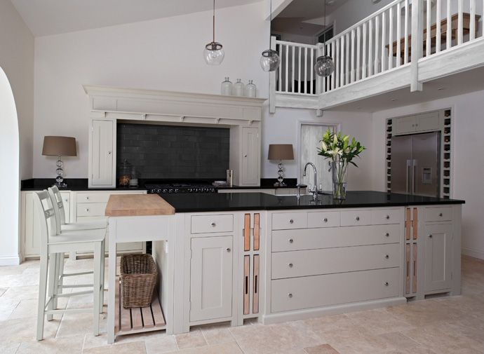 loft style kitchen with balcony overlooking....love the storage cubbies surrounding the frig, the pull out cutting blocks on the island & that amazing 'surround' framing the stovetop.