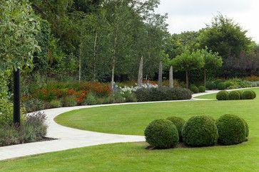 Grass Green Round Lawn, Curving round light stone path, round box balls, round sweeping beds with russet tangerine, red orange, purple, white.  Structure, shape, circles. Garden Design Ideas