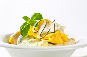 Spinach and ricotta stuffed pasta served with white cream sauce and grated Parmigiano