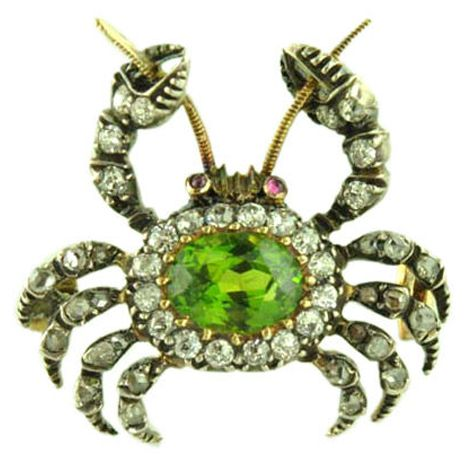 Crab-design brooch, England, ca.1900. Gold and silver, set with one oval-cut demantoid garnet, surrounded by old-cut diamonds, with diamond set legs and pincers, and cabochon ruby eyes