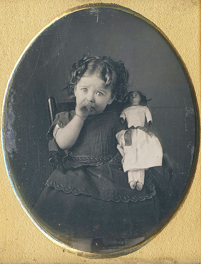 Antique photo of little girl sucking her thumb and holding her doll circa 1870 - 1890.