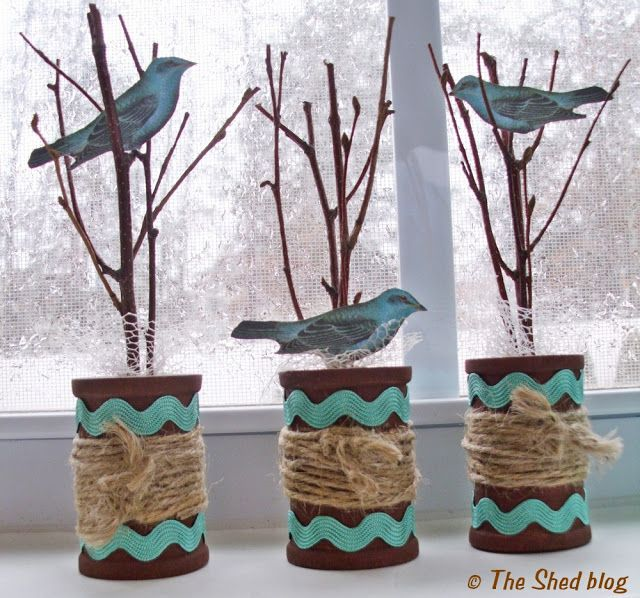 Covered coffee cans, with tree branches & birds inserted in lids.