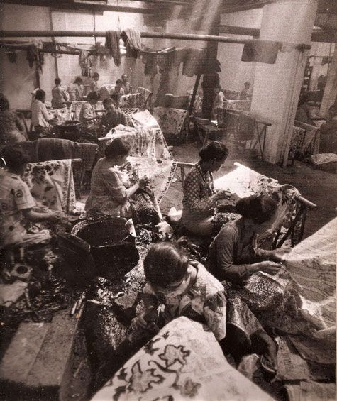 women in java sharing a pan of heated wax while each works on her own piece from batik fabled cloth of java
