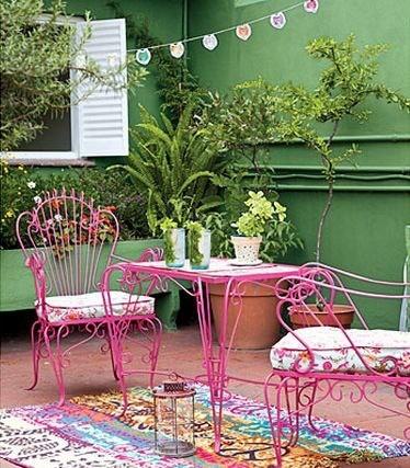 Mesa y sillas en rosa en contraste con la pared verde.