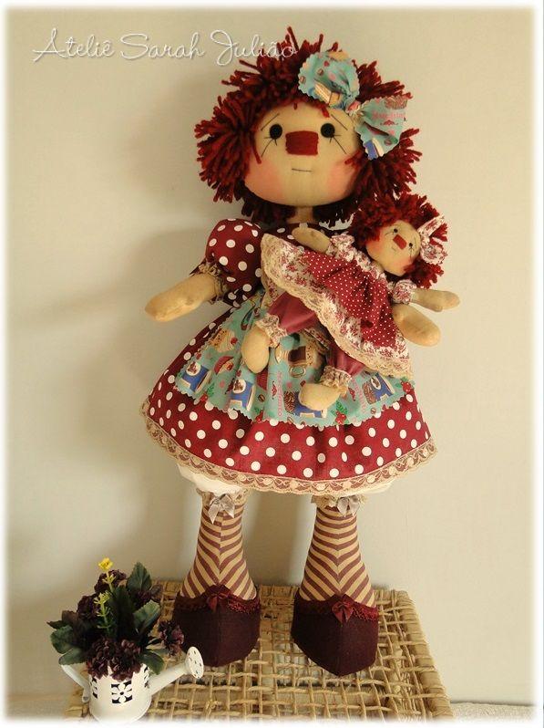 Boneca de pano estilo country, molde articulada (fica de pé e sentada). Pele colorida e aromatizada artesanalmente. Tem 50 cm de comprimento. Cabelos de lã vermelho, rosto bordado. Mini boneca Annie com 18 cm de comprimento. Versão criada pela artesã Millyta Vergara e produzida pelo o Ateliê Sarah Julião.