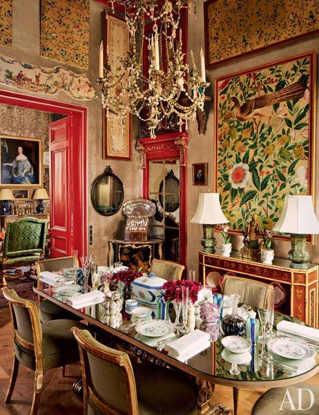 The dining area of a Paris apartment features Chinese painted-silk panels showcased against silver-leaf wallpaper.: