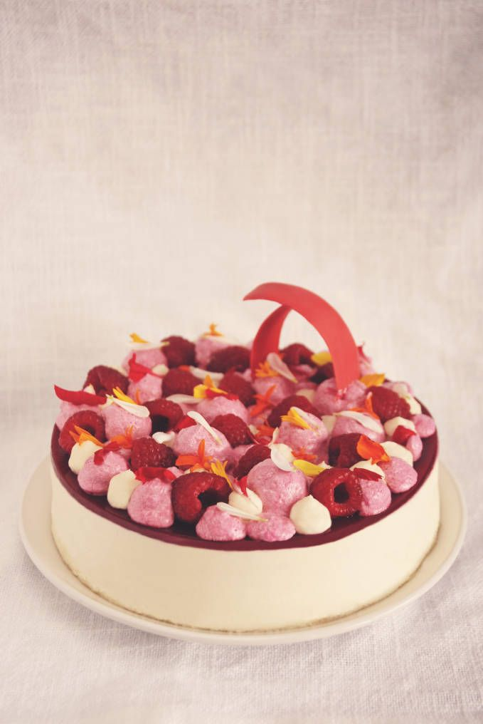 Raspberry and white chocolate entremet with almond dacquoise, white chocolate mousse, raspberry gel, raspberry mousse, whipped white chocolate and coconut ganache, fresh raspberries, and edible flowers. Click to get the recipe!