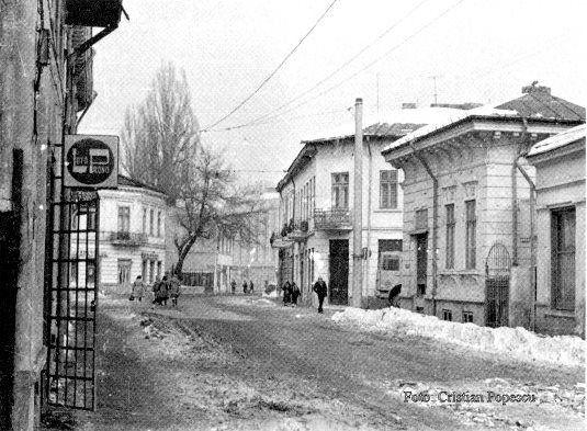 Calea Şerban Vodă, înaintea intersecţiei cu str. Bibescu Vodă. După o uşoară curbă la dreapta, începea piaţa, în configuraţia rămasă de pe timpul lui Carol al II-lea. Pe fundal se poate observa silueta magazinului Unirea. Fostele clădiri de pe traseul Bulevardului Unirii (I) | Bucurestii Vechi si Noi