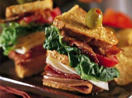 Receita de Club Sandwich - 2 colheres (sopa) de maionese, 6 fatias de peito de peru, 2 fatias de presunto, 4 fatias de bacon, 2 rodelas de tomate, 2 fatias de alface, 3 fatias de pão de forma