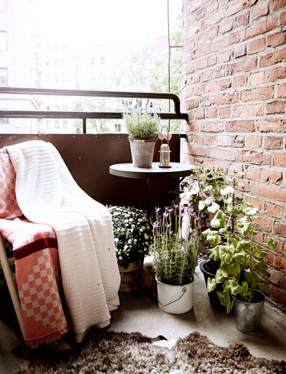 Inside a Chic Small Home With Major Style | DomaineHome.com // Cozy balcony space with plants, seating, and blankets.