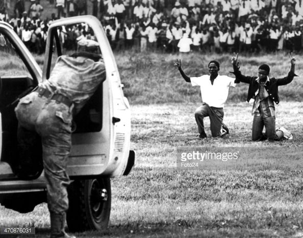 Soweto youths kneeling in front of the police holding their hands in the air showing the peace signon June 16, 1976, in Soweto, South Africa.