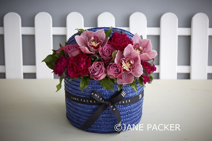 The Foal hatbox uses our brand new deep blue hatbox with complimentary deep pink and soft plum toned flowers and foliage. Matchpoint roses, vibrant magenta carnations, and cymbidium orchids sit amongst deep green berried ivy foliage.
