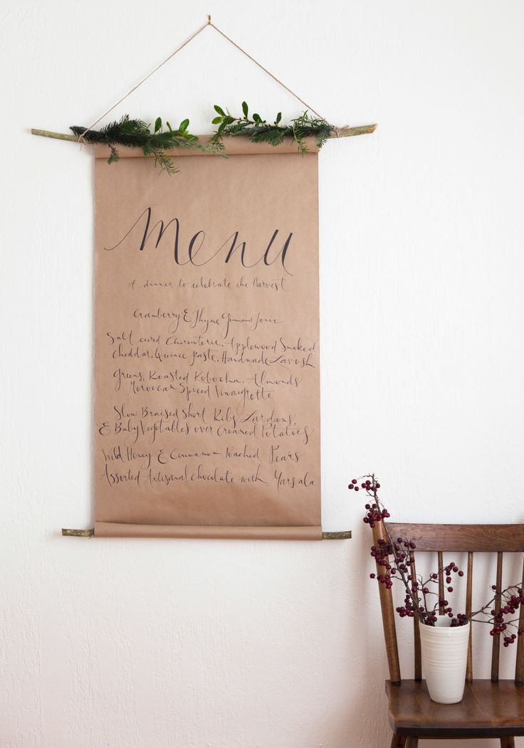 6 Holiday Decorations to Hang on Your Wall (That Aren't Wreaths) || Add a festive touch to your holiday dinner with this hanging menu. All you need is a branch, kraft paper, and a Sharpie for faux calligraphy.