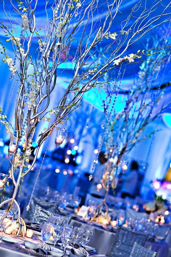 Winter wonderland, ice blue wedding featuring Tiffany white and Tiffany platinum linens, silver trees with hanging crystals and clear acrylic dining chairs | Linen Effects - Minneapolis, MN | Linen, table top decor and chair cover rentals. Photo by Kelly Brown Weddings.