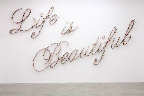 Life is Beautiful is written with hundreds of knives stabbing the walls at the Pinault Foundation's Palazzo Grassi, by Farhad Moshiri.
