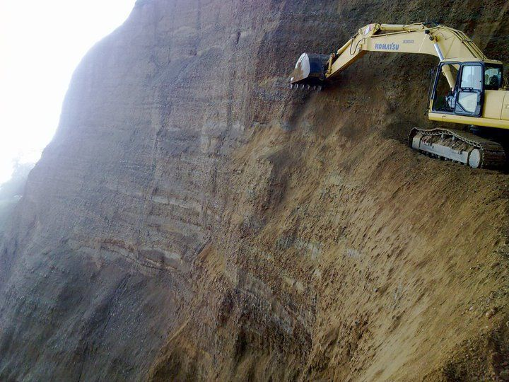 BUSINESS DANGERS AND OSHA VIOLATIONS - SCARY ROAD CONSTRUCTION ON THE SIDE OF A MOUNTAIN - EXCAVATOR CUTS ROAD OUT OF THE SIDE OF THE MOUNTA...