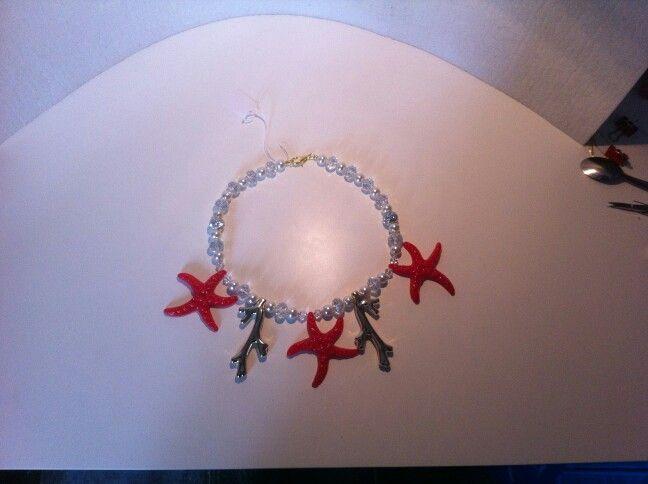 Collana con stelle marine rosse tipo corallo,rami di corallo color oro,perle di cristallo e bianche.