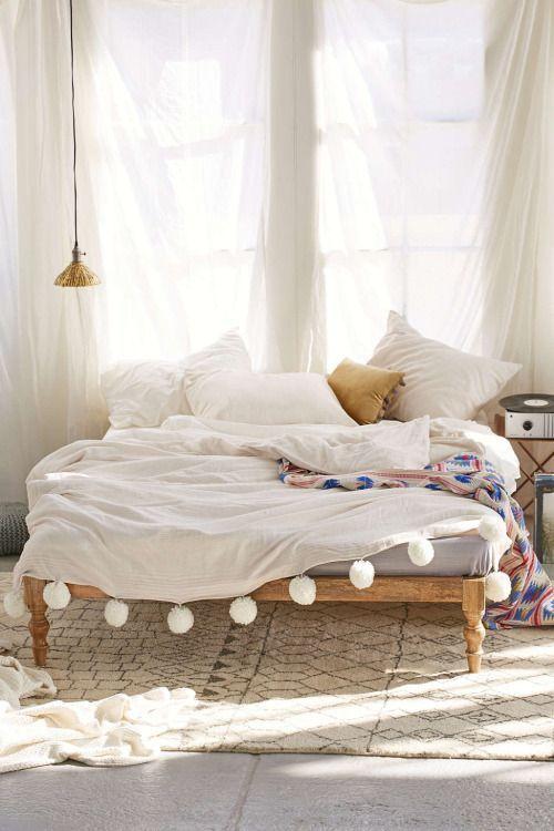 Cette décoration de chambre bohême est étonnamment épurée avec le blanc en couleur dominante. La couverture à pompons, les grands voilages informels et le plaid coloré à motif sur le lit font tout le style !