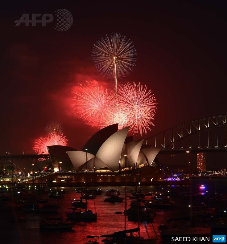 AUSTRALIA, Sydney: New Year's Eve fireworks erupt over Sydney's iconic Harbour Bridge and Opera House during the traditional early family fireworks show held before the main midnight event on December 31, 2014. AFP PHOTO / Saeed KHAN