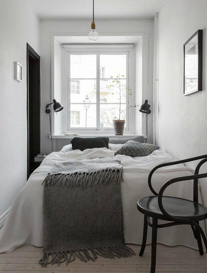 Στο μινιμαλιστικό υπνοδωμάτιο της φωτογραφίας, η κρεβατοκάμαρα έχει τοποθετηθεί ακριβώς μπροστά από το παράθυρο, ενώ τοποθέτησε δύο επιτοίχια φωτιστικά και ένα απλό ντουί με λάμπα στο ταβάνι.