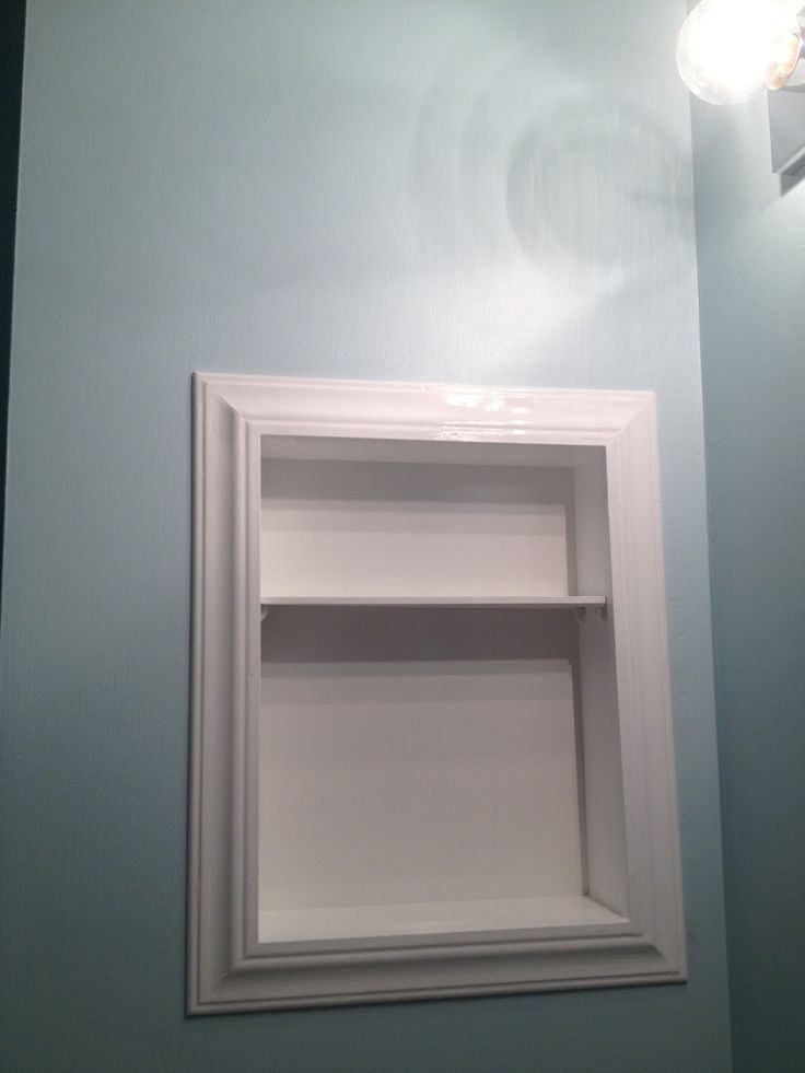 My husband turned our ugly old medicine cabinet into this pretty built-in shelf!