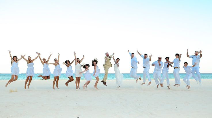 White wedding! The whole party wore white for this destination wedding and took a group jumping portrait on the beach. | Palace Resorts Weddings ®