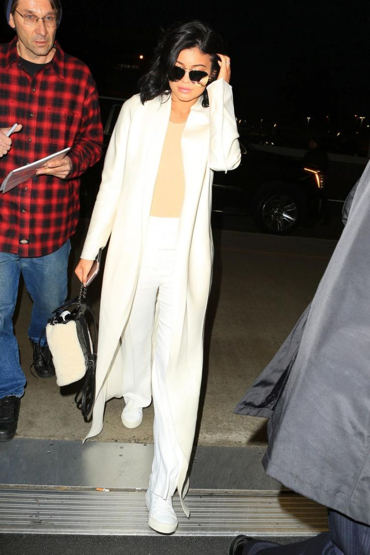 Kylie Jenner wearing Chanel Calfskin and Shearling Backpack, 3.1 Phillip Lim Shirred Waist Pants in Antique White, Maison Margiela Long Sleeve Bodysuit, The Row Nalaton Wool and Silk-Blend Coat and Victoria Beckham Classic Victoria Gold Mirrored Sunglasses