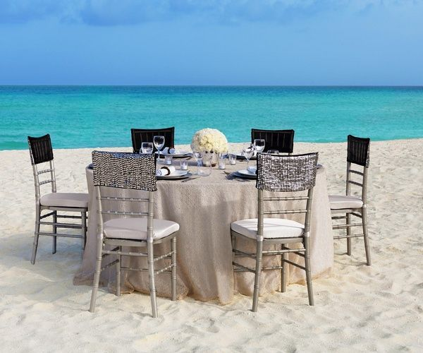 Linen, sequins and white floral centerpiece for neutral glam table setting at outdoor beach wedding reception | Metallic Sands Collection at Palace Resorts #destinationwedding