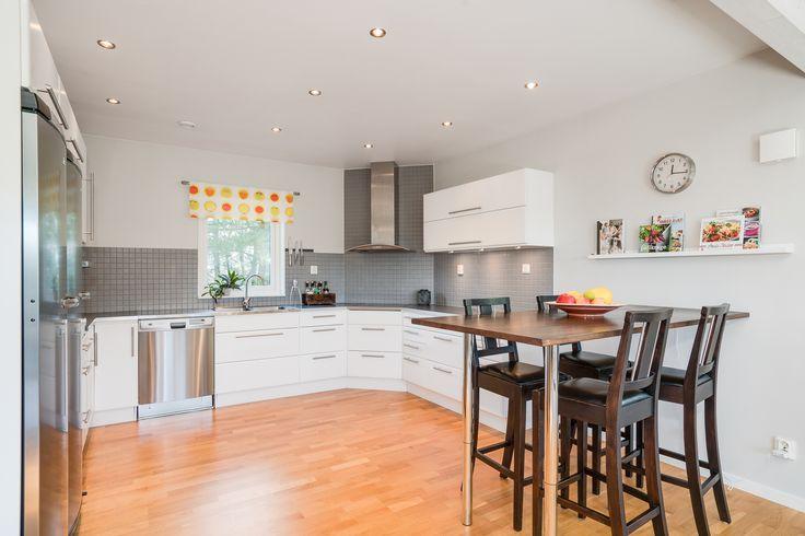 Köket går i grått och vitt med många spottar och rostfria kapitalvaror.