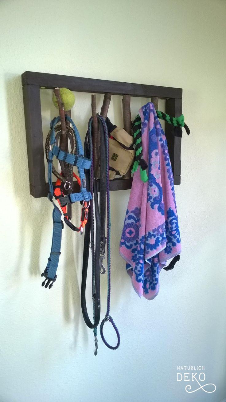 Die DIY-Garderobe aus Ästen im Holzrahmen. Zweige dienen als Halterung für Jacken, TAschen usw. Hier hängen an der selbstgebauten Garderobe Hundeleinen.
