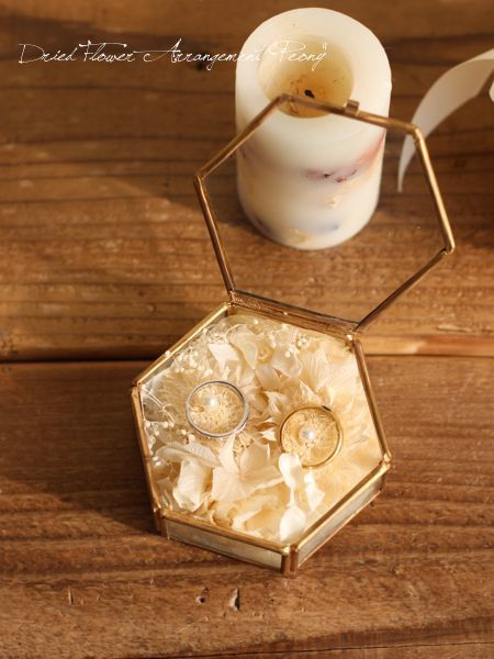 六角形の小さなガラスケースにプリザーブドフラワーでアレンジしたリングピローです。 挙式後もアクセサリーケースなどどしてお使い頂け、プレゼントにもおすすめのアイテムです。 箱にいれてお届け致します。