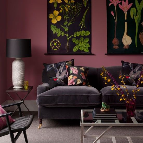 Smoky pink walls highlight dramatic vintage-style botanical prints, while vivid cushions lighten up a dark sofa.
