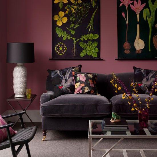 Smoky pink walls highlight dramatic vintage-style botanical prints, while vivid cushions lighten up a dark sofa.