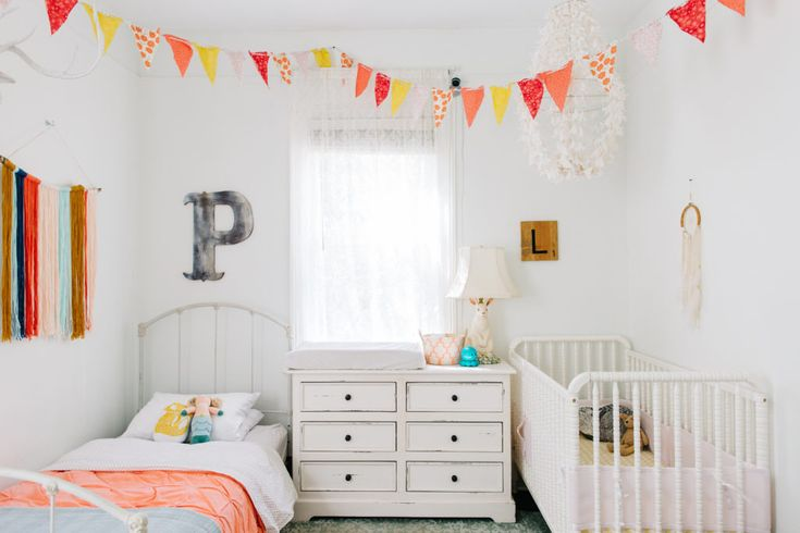 Shared Kid's Room Ideas: A nursery and a big kid's room in one! This room features polka dot bunting, a vintage bed frame, and a shabby chic dresser.
