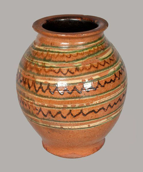 Sold $ 4,000 Extremely Rare Ovoid Redware Jar with Elaborate Three-Color Slip Decoration, attributed to John Bell, Chambersburg, PA, circa 1829, ovoid jar with concave collar molding and flattened rim, the surface profusely-decorated with stripes of copper and yellow slip interspersed with wavy manganese trails and covered in a clear lead glaze. Lead-and-manganese-glazed interior. This jar is discussed in H.E. Comstock's The Pottery of the Shenandoah Valley Region,
