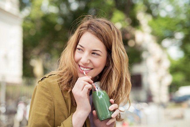 Una joven mujer bebiendo un batido verde que impulsa la serotonina en todo el cuerpo
