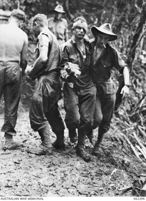 Private R. J. Rowe assists Corporal M. Hall, DCM, of the 2/16th Battalion to the regimental aid post after an attack on Shaggy Ridge. Reference number 062294