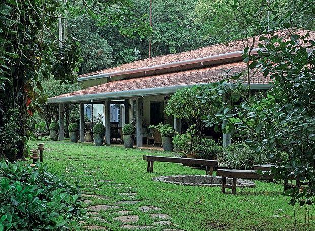 Jardim que parece mata preservadaO fogo de chão com bancos de madeira é um convite para relaxar nos dias frios. Em primeiro plano, clúsia (Foto: Raphael Briest/Divulgação)