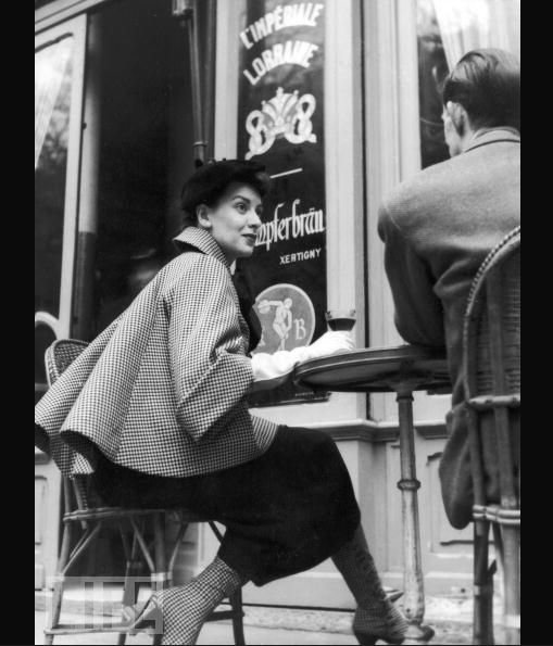 Dior - 1954, outside a Paris cafe a model wears matching check coat and spats