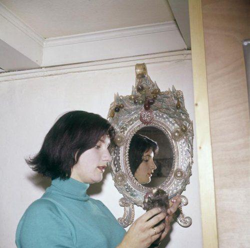 Nelly Frijda-Wiegel ( 1936) Nederlands actrice en politica. Foto: Nelly Frijda   poseert voor een spiegel met een uitbundige barokrand met glazen ornamenten.   Nederland jaren '60.