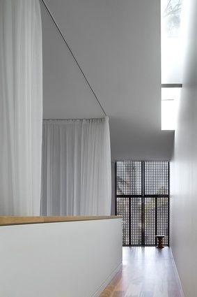 A perforated screen on the first-floor facade and a narrow skylight cast streams of light onto the pristine interior surfaces.