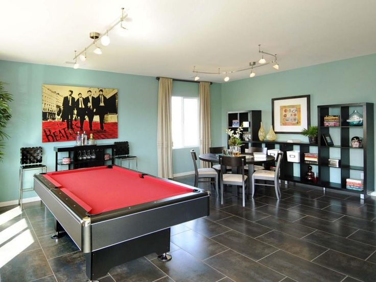 The light blue and red color palette in this game room gives it a fun, retro feel. Modern track lighting provides visual separation for the two distinct areas of the room.