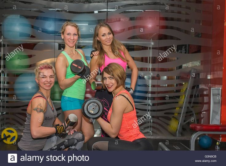 Download this stock image: Four young athletes in the gym with weights. - G3N9CB from Alamy's library of millions of high resolution stock photos, illustrations and vectors.
