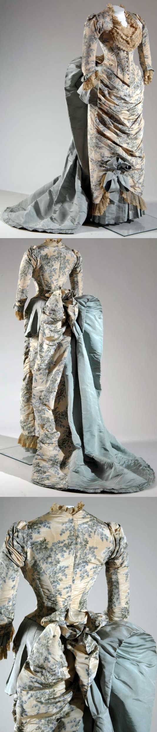 Evening dress, Worth, 1883. Light blue white floral silk moiré. Bodice has scooped neckline, pleating at shoulders, 3/4 sleeves. Lace trimming at neckline cuffs; additional light blue faille trimming at cuffs. Center front button closure. Skirt has pleated front panel. Large light blue faille bow near bottom hem. Large bustle uses blue white moir on proper left side and blue faille on proper right; bustle extends to become a train. Skirt hem trimmed w/lace pleated blue faille.